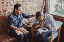 men with heads bowed in prayer at a Bible study
