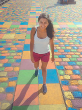 A young woman walks on pavement that is painted in different colors.