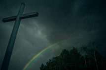 a gray cross and a rainbow in the sky