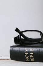 Reading glasses on top of closed Bible laying on wooden table.