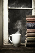 Steaming cup of coffee on a wood table next to a stack of books and bible