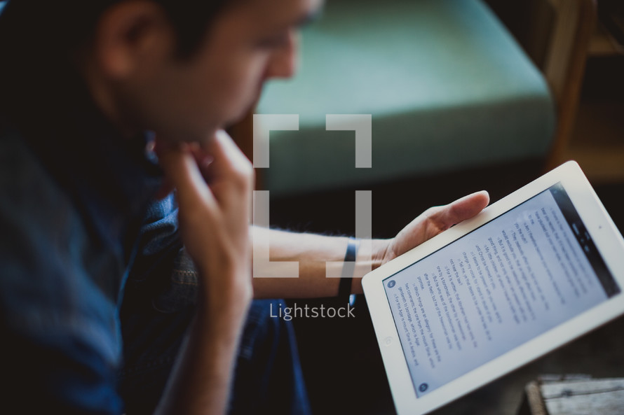 man reading a Bible on an iPad