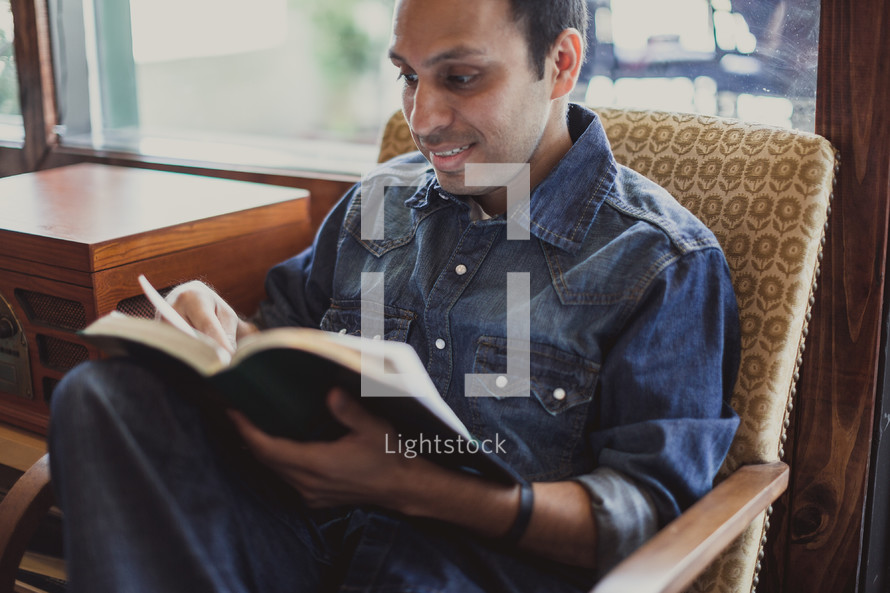 Smiling man reading the Bible.