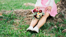 a woman sitting in the grass with a bouquet of flowers in her lap