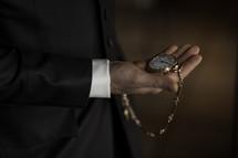 a man holding a gold pocket watch
