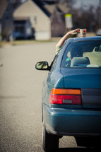 woman reaching for a coffee cup that she left on her car roof