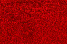 Red background with leather texture. Blank backdrop with a surface of the red skin.