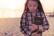 young girl thinking, standing on the beach holding her bible at sunset