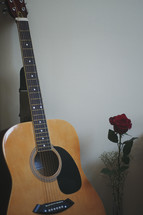 guitar and red rose in a vase