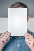 Man holding up a blank page or book cover hiding his face.