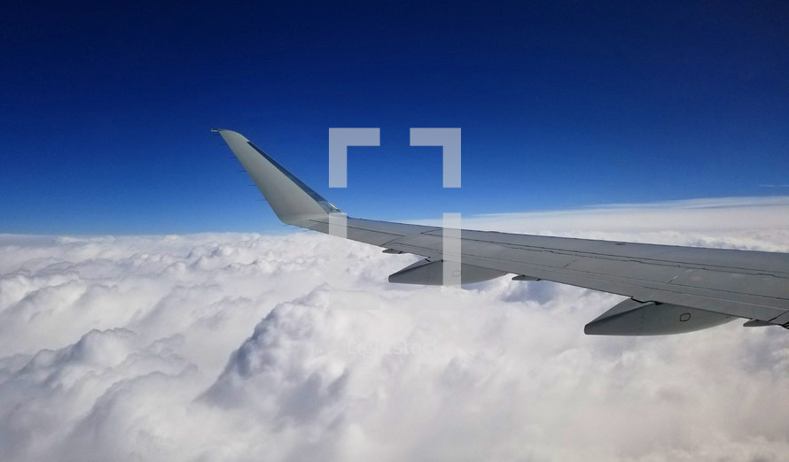 wing of an airplane over clouds