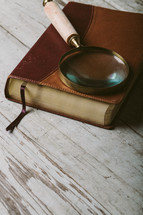 Magnifying glass on top of closed Bible laying on wooden table.