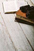 Binoculars on top of stack of Bibles, laying on wooden table with open Bible.