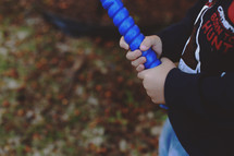 a boy child holding a plastic baseball bat