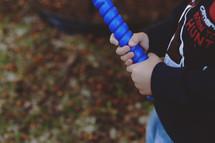 a boy child holding a plastic baseball bat
