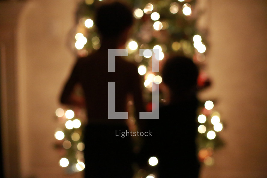 children standing in front of a Christmas tree