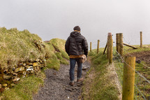 man hiking on a path on the cliffs of moher