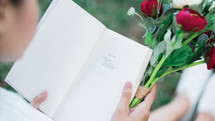 a woman reading a book holding a bouquet of flowers