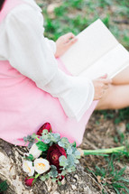 a girl sitting in the grass reading a book next to a bouquet of flowers