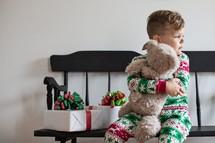 toddler boy hugging a teddy bear at Christmas