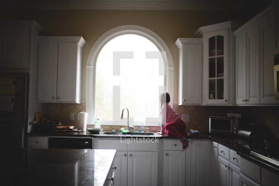 a little girl sitting on a kitchen counter and looking out a window