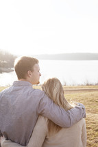 couple standing together outdoors by a lake