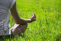 woman meditating sitting in grass