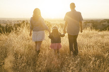 a family standing in a field of tall grasses