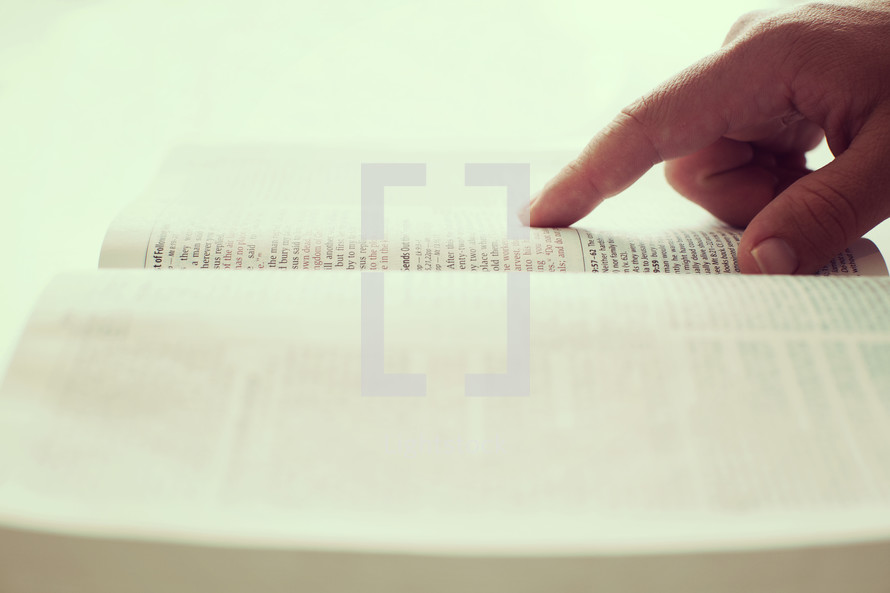 finger pointing on the pages of a Bible