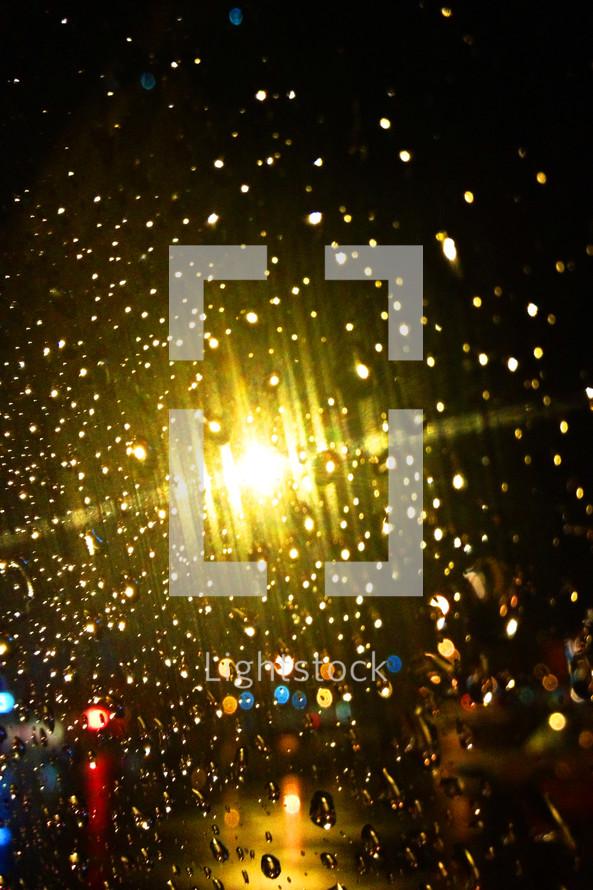Lights shining through raindrops on a window.