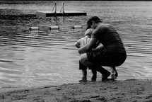 father and son squatting at the edge of a lake