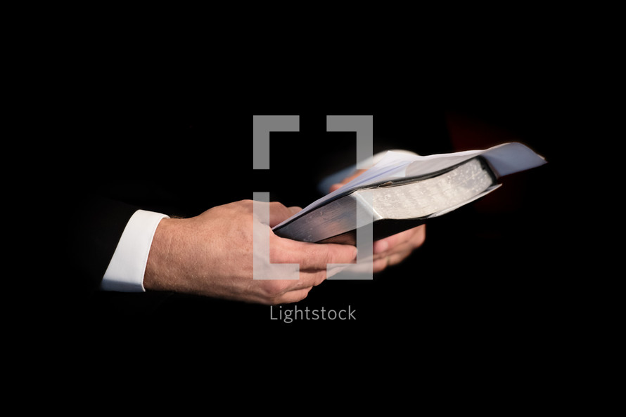 Hands holding a Bible and sermon notes.
