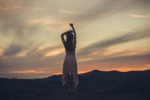 a woman stretching at sunset