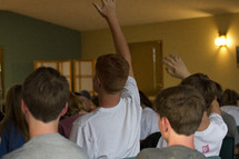 boys with hands raised in a room