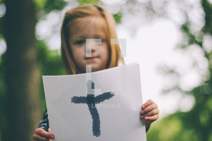 girl holding a cross on paper