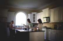 mother and daughters making breakfast in a kitchen