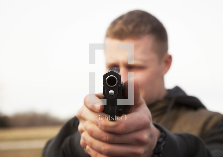 a man pointing his hand gun