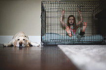 a little girl in a dog cage and a sleeping dog