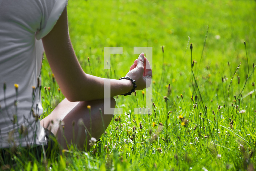 woman meditating sitting in grass