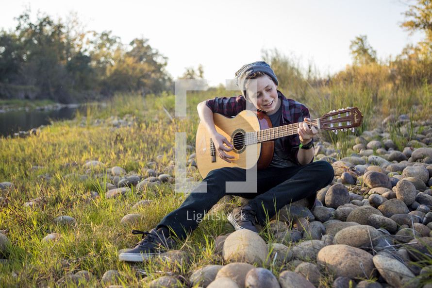 boy playing a guitar outdoors