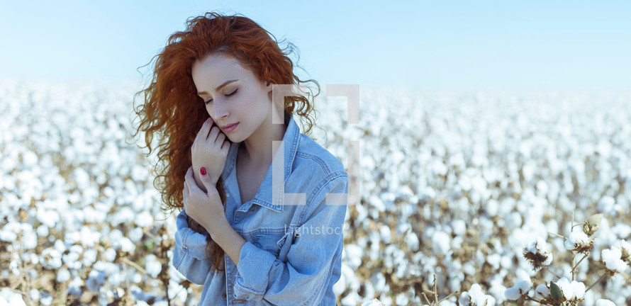 a woman standing in a field of cotton