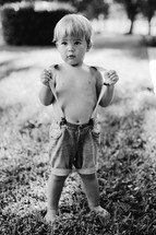 a bare chested toddler boy in suspenders standing in the grass