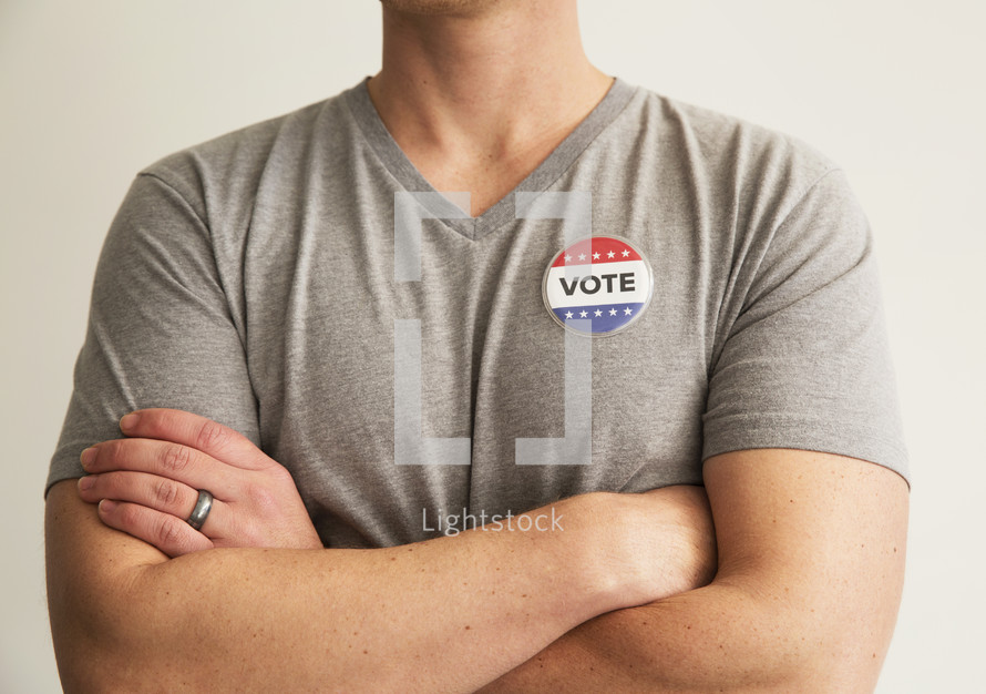 """A man in a gray t-shirt wearing a button reading, """"Vote."""""""