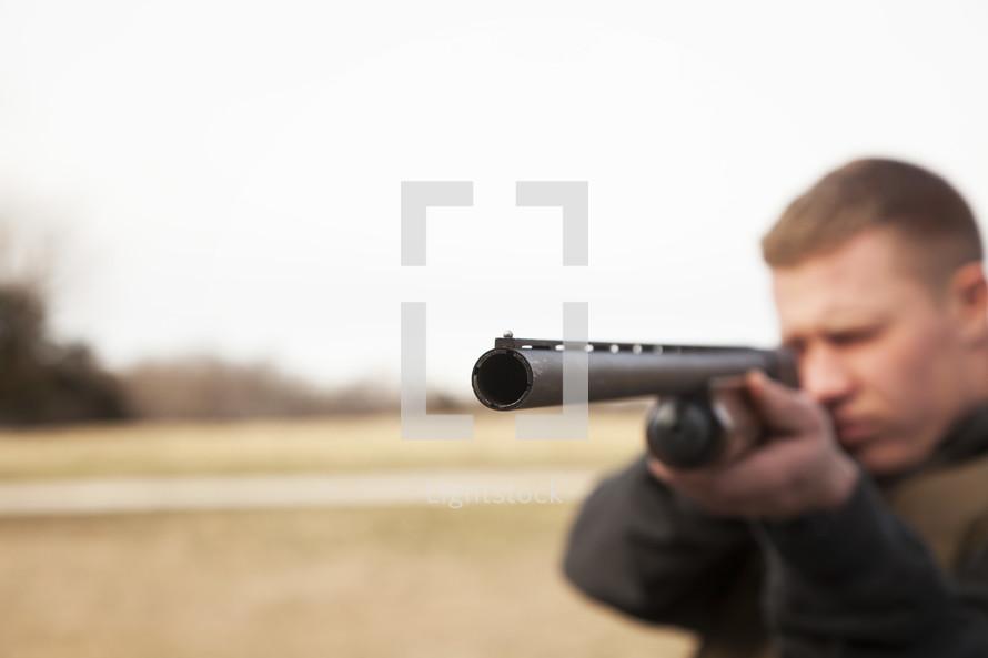 a man pointing a shot gun