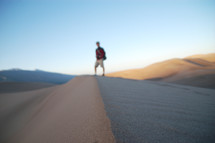 A hiker stands on the tip of a sand dune.