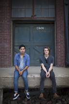 Two men sitting on a stoop in front of a warehouse