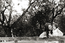 A woman and child on a wooden fence smiling mom and daughter