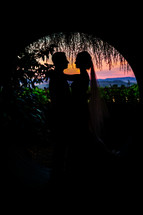 A bride and groom silhouette wedding sunset tunnel
