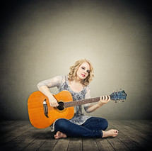 woman sitting on stage playing a guitar