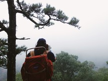 Hiker with a backpack by a pine tree in the mountains at dawn.